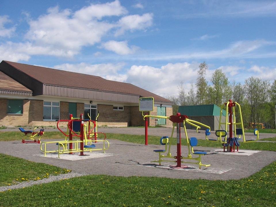 Photo du parc (sans personne) : derrière ce qui ressemble à une école, quatre jeux en métal pour enfants, de couleurs jaune et rouge.